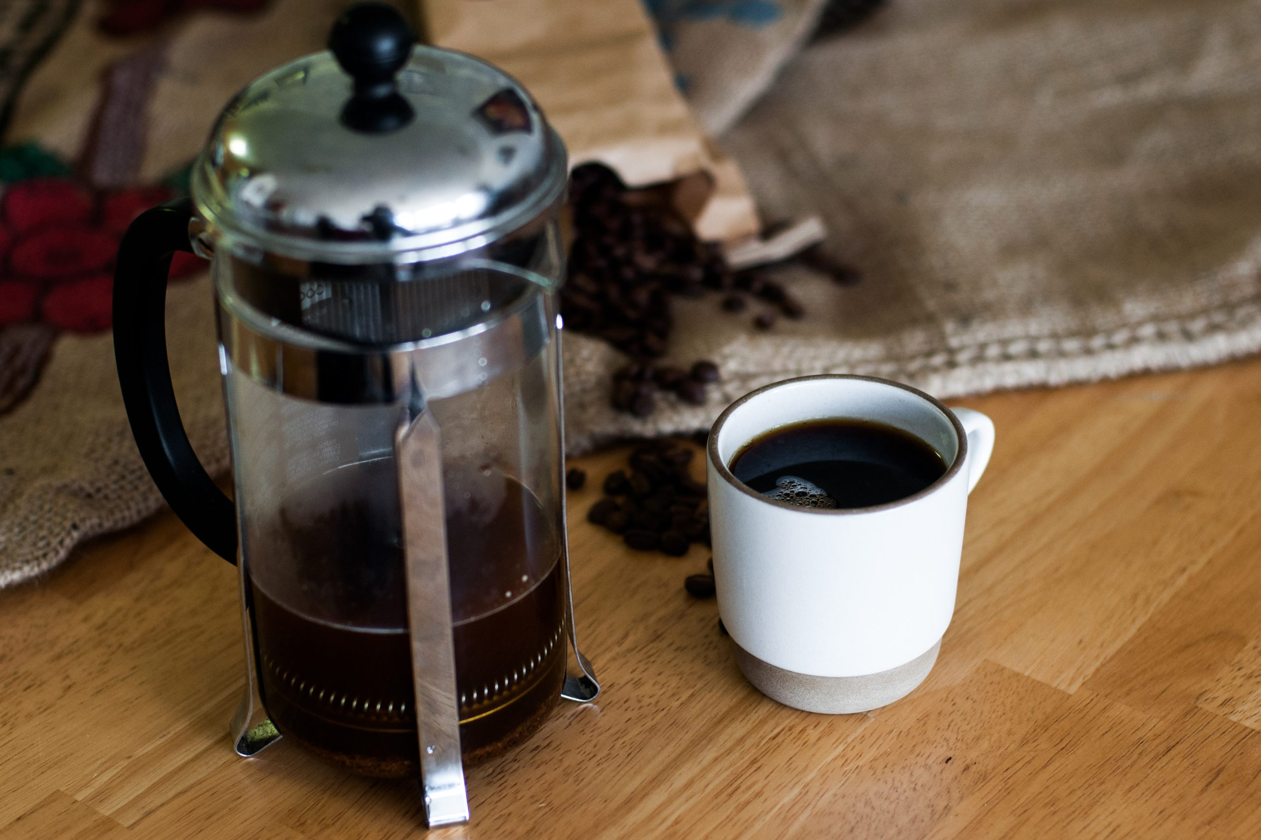 french press with a cup of black coffee sit on wood surface table with coffee beans spread out