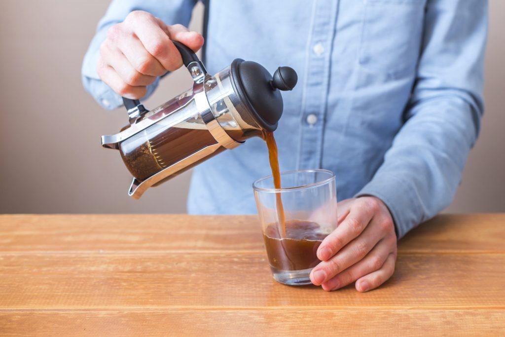 seorang lelaki berkemeja biru menuangkan kopi hitam hasil seduhannya dari french press ke dalam gelas